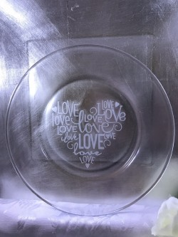 "$15 - Cake Plate 7.5"" round with the words ""love"" in a heart shape sand carved into the plate."